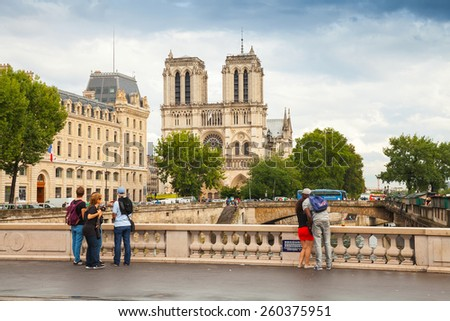 Paris, France - August 07, 2014: Street view of Pont Saint-Michel. Bridge across Seine river with walking people and Notre Dame de Paris cathedral on a background - stock photo