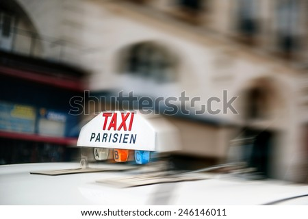 PARIS, FRANCE - AUGUST 18, 2014: Taxi sign on top of a cab vehicle in motion as seen in Paris, France - stock photo