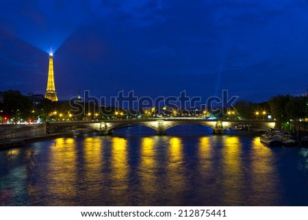 PARIS, FRANCE - AUGUST 6TH 2014: A view at dusk taking in the sights of the Eiffel Tower and Pont des Invalides in Paris on 6th August 2014. - stock photo