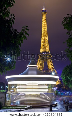 PARIS, FRANCE - AUGUST 8TH 2014: A vintage Carousel with the Eiffel Tower in the background in Paris on the 8th August 2014. - stock photo