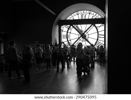 Paris, France - August 10, 2014: Tourists and visitors near the famous ancient clock window in Orsay Museum, black and white photo - stock photo