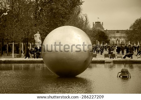 PARIS, FRANCE - DECEMBER 1, 2013: Golden Sphere by James Lee Byars is exhibited in Tuileries garden near Louvre museum.  Byars was specialized in installation sculpture and in performance art. - stock photo