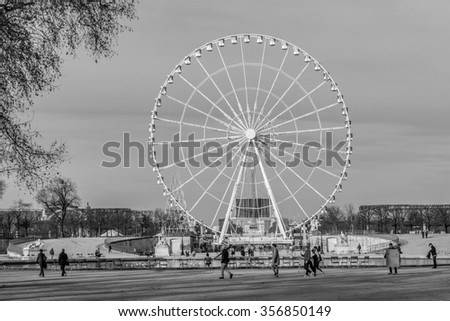 PARIS, FRANCE - DECEMBER 16, 2015: Parisians and Tourist in famous Tuileries garden. Tuileries Garden is a public garden located between Louvre Museum and Place de la Concorde. Black and white. - stock photo