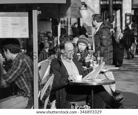 PARIS, FRANCE - DECEMBER 8, 2013: Parisians and tourists sit on terrace of  cafe at Place de la Bastille. Cafes in Paris appear to be an important cultural and socializing institutions.