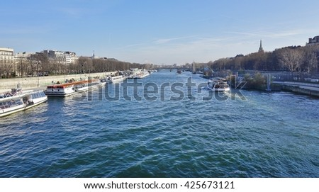 PARIS, FRANCE -26 DECEMBER 2015- Peniche and tourist boats on the river Seine in Paris between the Right and the Left banks.