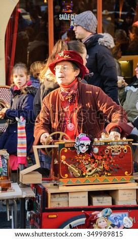 PARIS, FRANCE - DECEMBER 29, 2013:  Street artist Arlette Denis (Macadam Manivelle) singing and playing barrel organ at Montmartre. - stock photo