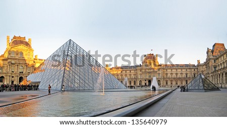 PARIS, FRANCE-DECEMBER 24: The kings palace louvre with its famous pyramid on December 24, 2012. Louvre is the biggest Museum in Paris displayed over 60,000 sq.M. of exhibition space. - stock photo