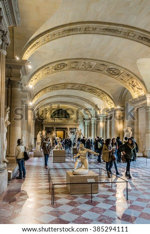 PARIS, FRANCE - DECEMBER 22, 2014: Tourists visit Louvre Museum. Louvre Museum is one of the largest and most visited museums worldwide.