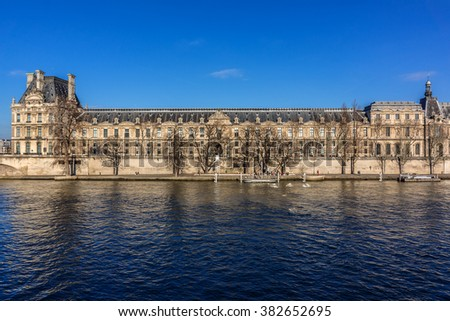 PARIS, FRANCE - DECEMBER 31, 2014: View of Louvre Museum from River Seine at sunset. Louvre Museum is one of the largest and most visited museums worldwide. - stock photo