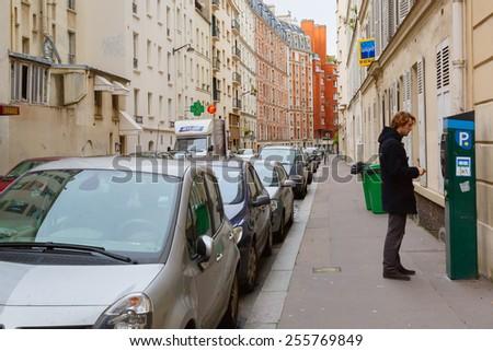 Paris, France - December 22, 2014: Young man paying at parking meter on Paris street - stock photo