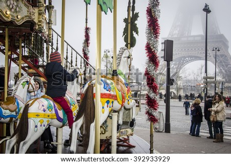 PARIS, FRANCE - DECEMBER 7, 2014: Youngsters enjoy the carousel while many adults make their way to and from the Eiffel tower, in Paris France - stock photo