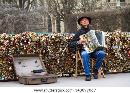 PARIS, FRANCE - FEBRUARY 18, 2014: Accordion player on the Pont de l'Archeveche (Archbishop's Bridge) at the Notre-Dame in Paris, France, on February 18, 2014 - stock photo