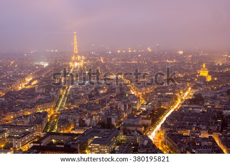 PARIS, FRANCE - FEBRUARY, 13, 2016: Aerial view of Paris with Eiffel tower on the stormy rainy night in the winter season, with cloudy and fog, looking from Montparnasse tower. - stock photo