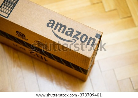 PARIS, FRANCE - JAN 28, 2016: Amazon logotype printed on cardboard box side seen from above on a wooden parwuet floor. Amazon is an American electronic e-commerce company distribution worlwide - stock photo