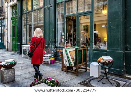PARIS, FRANCE - JAN 3, 2014: Antique shop on a side street in the historic neighborhood of Le Marais. Items for sale on the sidewalk. An unidentified woman in a red coat walks by. - stock photo