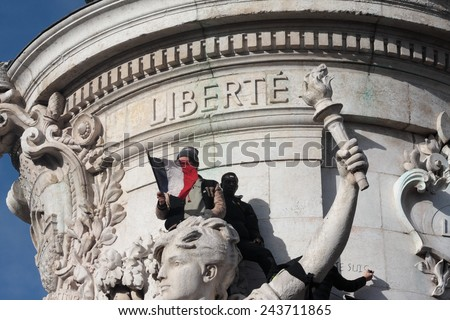 PARIS, FRANCE-JANUARY 11, 2015: Black and arab people waving french flag during manifestation on Republic Square in Paris against terrorism and in memory of the attack against Charlie Hebdo.  - stock photo