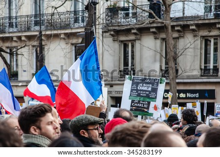 "Paris, France - January 11, 2015: Close up of crowd with french flag and ""Je suis Charlie"" in different language during the anti-terrorism rally in Paris. - stock photo"