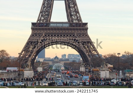 Paris, France - January 1, 2015: Eiffel Tower at sunset. The tower is the most famous and popular tourist attraction in Paris. - stock photo