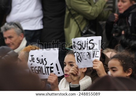 PARIS, FRANCE-JANUARY 11, 2015: Girl displaying slogans advocating equality and fraternity during manifestation in Paris against terrorism and in memory of the attack against Charlie Hebdo.  - stock photo