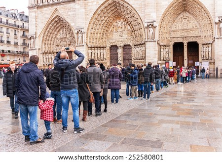 Paris, France - January 9, 2015:  Long queue (crowd) of people waiting in line to Notre Dame de Paris. People queueing in front of entrance.  Notre Dame is one of the most popular destinations.  - stock photo