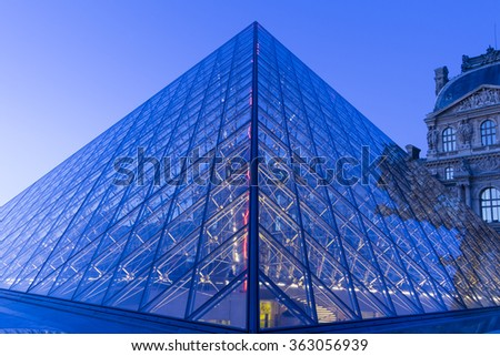 Paris, France-January 15, 2016 : The Louvre Pyramid based in the main courtyard(cour Napoleon) of the Louvre Palace in Paris, France.It serves as the main entrance to the Louvre museum. - stock photo