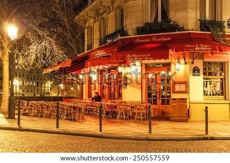 Paris, France - January 8, 2015. Traditional parisian cafe near famous Notre Dame de Paris in the evening. Wicker furniture is on the pavement. Travel (vacation),  cuisine concept. France. - stock photo