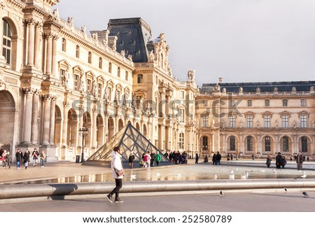 Paris, France - January 11, 2015: View of main courtyard of Louvre Museum with pyramid on a sunny day. Louvre Museum is one of the largest museums in the world.  - stock photo