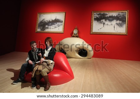 PARIS, FRANCE - JANUARY 7, 2013: Visitors take a picture as they sit at the Mae West Lips Sofa by Salvador Dali displayed at his retrospective exhibition in Paris, France. - stock photo