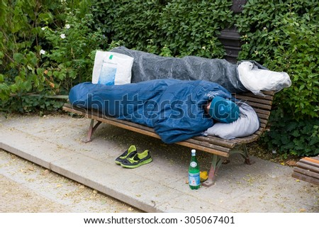 PARIS, FRANCE - JULY 27, 2015: A homeless man is sleeping on a bench in a park in Paris in France - stock photo