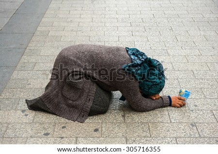 PARIS, FRANCE - JULY 28, 2015: A homeless woman is begging for money on the Champs-Elysees in Paris in France - stock photo