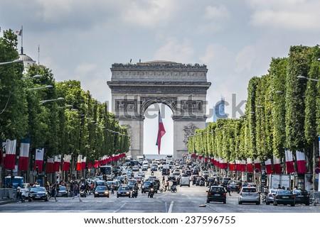 PARIS, FRANCE - JULY 14, 2014: Arc de Triomphe de l'Etoile - one of most famous monuments in Paris on French National Day (Bastille Day). Arc de Triomphe was built in 1806 - 1836 by architect Jean. - stock photo