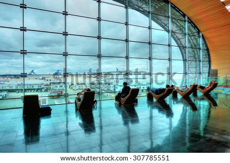 Paris, France - July 27, 2015 : Charles de Gaulle International Airport Travelers sit on sofas in the airport waiting hall - stock photo