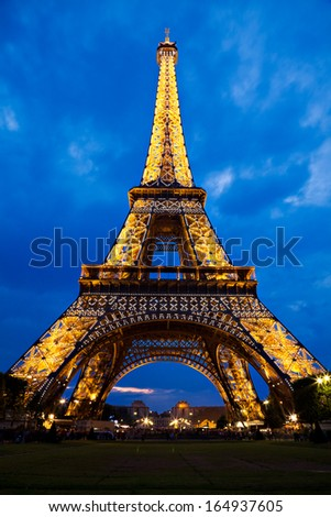 PARIS, FRANCE - JULY 21: Eiffel Tower lights up at twilight on July 21, 2011 in Paris, France. Also nicknamed the Iron Lady, it is one of the most recognizable monuments in the world. - stock photo