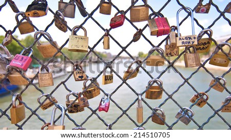 PARIS, FRANCE - JULY 7: Love locks placed by tourists on the Pont des Arts on the river Seine, on July 7, 2011 in Paris, France. - stock photo