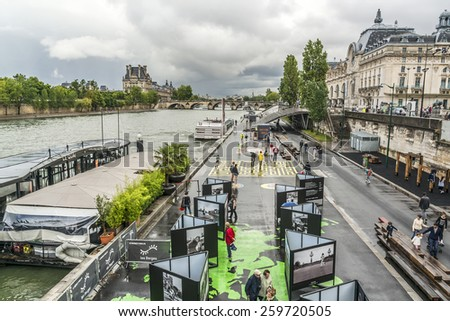PARIS, FRANCE - JULY 13, 2014: Outdoor Activities in Paris - Les Berges de Seine. Les Berges (opened in 2013) is a 2 km pedestrian area along the Left Bank between the Musee d'Orsay and Pont d'Alma. - stock photo