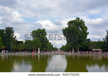 Paris, France - July 26, 2013: Parisians rest around a lake in The Tuileries Gardens on a hot stormy summer day in Paris. In the distance is The Louvre Art Gallery & Museum.