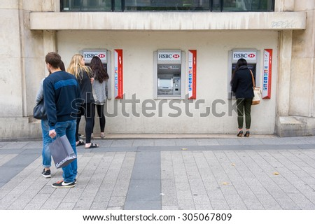 PARIS, FRANCE - JULY 28, 2015: People waiting for an ATM machine to withdraw money on a street in Paris in France. - stock photo