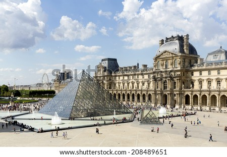 PARIS, FRANCE- JULY 29: The large glass pyramid and the main courtyard of the Louvre Museum on July 29, 2014. The Louvre Museum is one of the largest museums of the world - stock photo