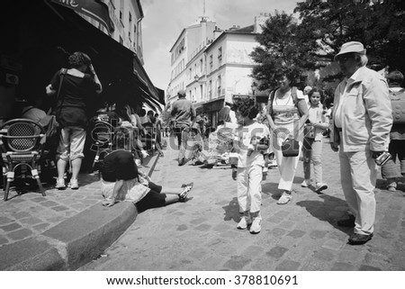 PARIS, FRANCE - JULY 22, 2011: Tourists in Montmartre district on July 22, 2011 in Paris, France. Monmartre area is popular among tourists in Paris, the most visited city worldwide.