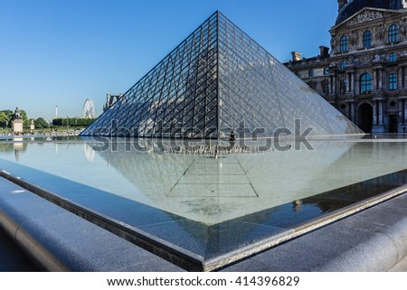 PARIS, FRANCE - JULY 16, 2012: View of pyramid and fountain at courtyard of Louvre Museum. Louvre Museum is one of the largest and most visited museums worldwide. - stock photo