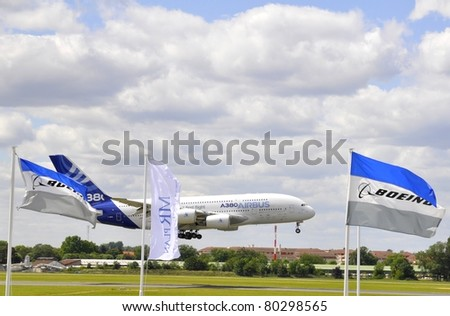 PARIS, FRANCE - JUNE 24: A380 aircraft landing  behind competitor Boeing flag during the International Paris Air Show. June 24, 2011 Le Bourget Airport, France. - stock photo