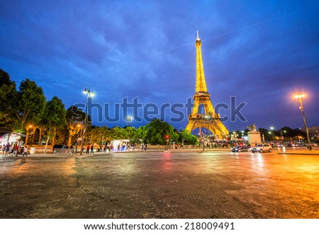 PARIS, FRANCE - JUNE 17, 2014: Eiffel Tower night lights with tourists in the streets. The landmark is the most visited paid monument in the world. - stock photo