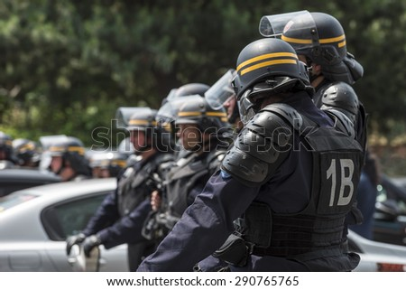 PARIS, FRANCE - JUNE  25, 2015 :  French police (riot squad) try to control the protest of the taxi drivers against the service Ubber Pop at the Porte Maillot. - stock photo