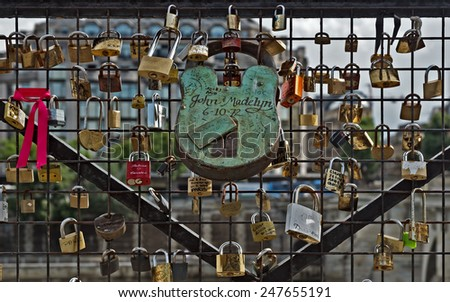 PARIS, FRANCE - JUNE 9, 2014: Love Padlocks at Pont des Arts over the river Seine. The thousands of locks of loving couples symbolize love forever.  - stock photo