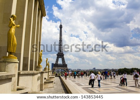 PARIS, FRANCE - JUNE 6 : Palais de Chaillot, Golden statues and Eiffel tower on the background - tourists and Parisians walking at the esplanade of Trocadero on June 6th 2013 in Paris, France - stock photo
