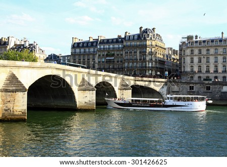 PARIS, FRANCE - JUNE 24, 2015: Pleasure boat floating on the Seine in the background of the Royal Bridge.