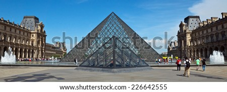 PARIS, FRANCE - JUNE 9, 2014: Pyramid near Louvre Museum. Louvre is one of the biggest Museum in the world, receiving more than 8 million visitors each year.  - stock photo