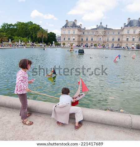 PARIS, FRANCE - JUNE 15 : Two Children sailing the toy boat in the pond of Luxembourg Palace garden, summer season on June 15, 2014 in Paris, France - stock photo