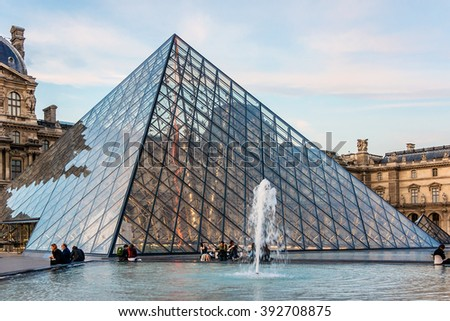 PARIS, FRANCE - JUNE 10, 2015: View of famous Louvre Museum with fountains in courtyard of Louvre Palace at evening. Louvre Museum is one of the largest and most visited museums worldwide.