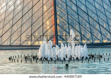 PARIS, FRANCE - JUNE 10, 2015: View of famous Louvre Museum with fountains in courtyard of Louvre Palace at evening. Louvre Museum is one of the largest and most visited museums worldwide. - stock photo